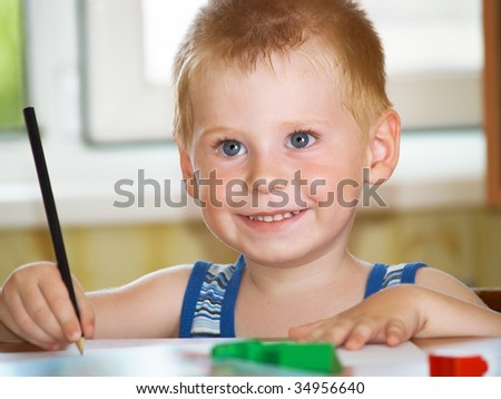 The boy of 2 years draw in a children's room - stock photo