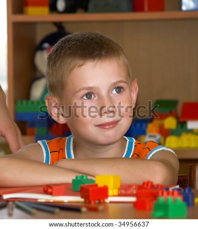 The boy of 7 years is engaged in a children's room - stock photo