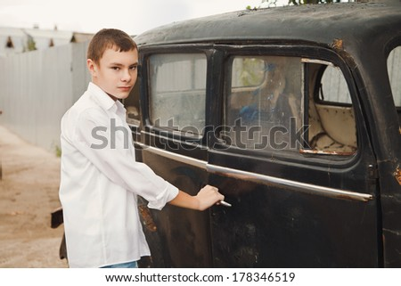 the boy opens a door of the old rusty car