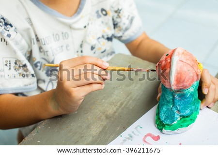 The boy painting watercolor on plaster doll