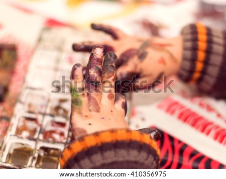 the boy paints with watercolors on paper, dirty hands - stock photo