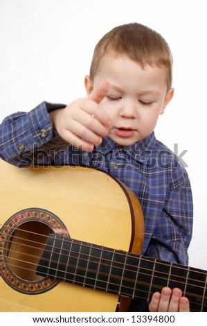 The boy plays an acoustic guitar - stock photo