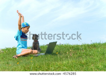 The boy plays on laptop with a dog - stock photo