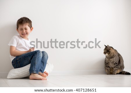 the boy plays with a cat of the house - stock photo