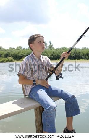 The boy pulls a fish - stock photo