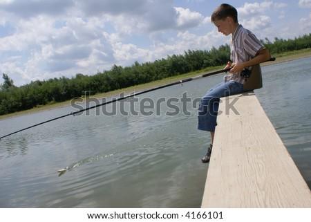 The boy pulls a fish to coast - stock photo