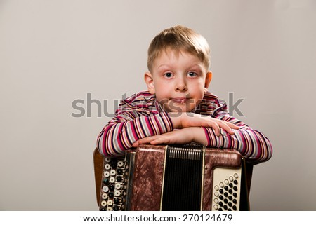 The boy put his hands together and leaned on the accordion - stock photo