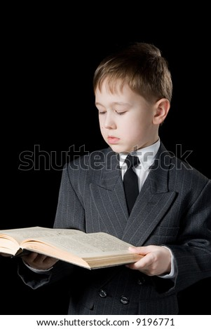 The boy reads the book. A black background. - stock photo