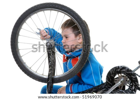 The boy repairs the bicycle