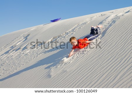 The boy rolled down the slope of snow-white dunes of gypsum sand.  White Sands National Monument, NM - stock photo