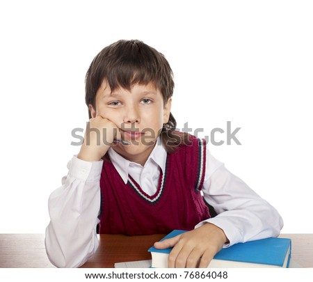 The boy sits in a class at desktop over the book - stock photo