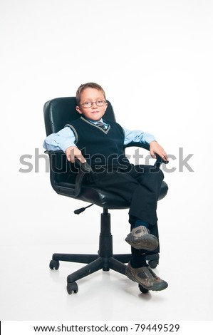 The boy sits in a management armchair on a white background - stock photo
