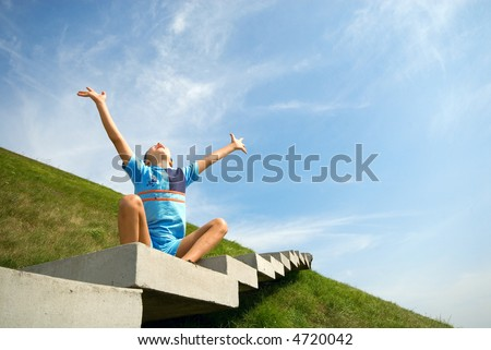 The boy sits on a green grass and looks in sky - stock photo