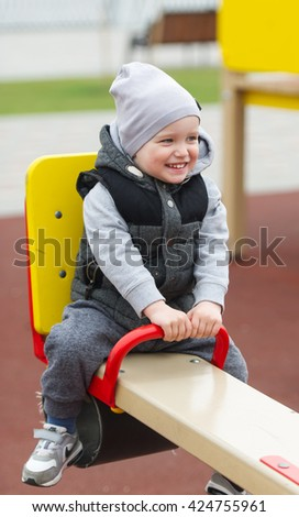 The boy sits on a swing. Rest in an amusement park. - stock photo