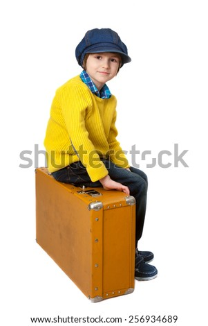 the boy sits on the old suitcase