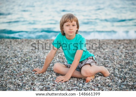 The boy sits on the shore of the sea. Summer  photo-shoot
