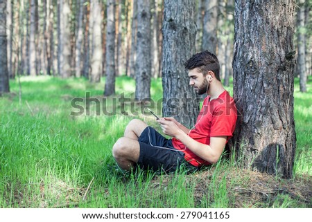 The boy sits under a tree and reads the book