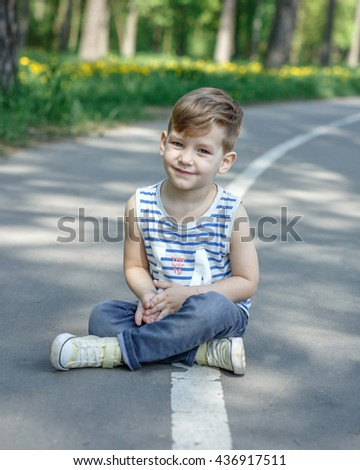 the boy sitting on the ground - stock photo