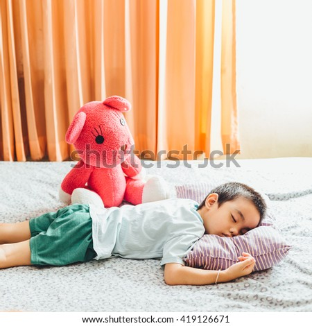 the boy sleeping on the bed with doll