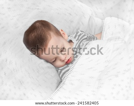 the boy sleeps, with snowflakes - stock photo