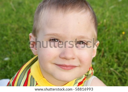The boy smiles, background green grass,portrait - stock photo
