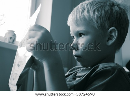 The boy studying a leaflet - stock photo