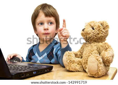The boy teaches a toy bear in front of the laptop - stock photo