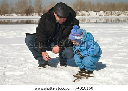 The boy, the child with the father on on winter fishing - stock photo