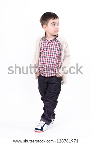 the boy walking with one leg outstretched forward standing with his hands in his pockets in shirts and trousers, and looking up to the right