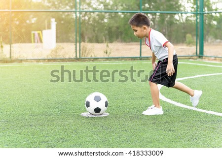 The boy was playing soccer on the football field with happiness. - stock photo