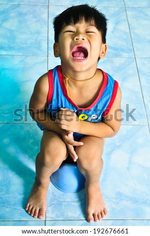 The boy was sitting on the pot.  - stock photo