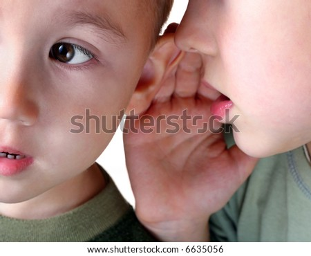 The boy whispering in an ear to the younger brother. - stock photo