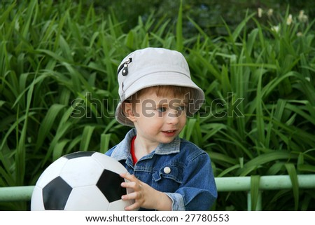 The boy with a ball in hands on a background of a green grass
