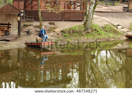 The boy with a fishing pole sitting on the pier near the pond