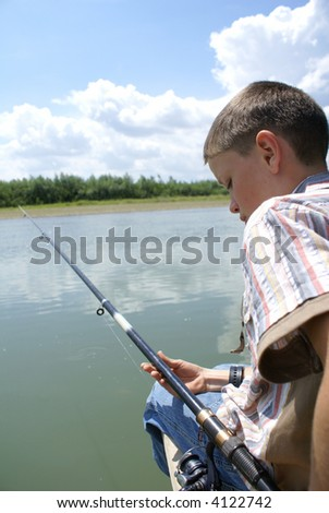 The boy with a fishing tackle on coast of the river - stock photo
