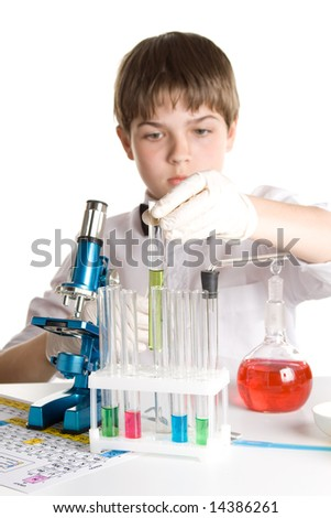 The boy with a microscope and various colorful flasks on a white background. Selective focus.