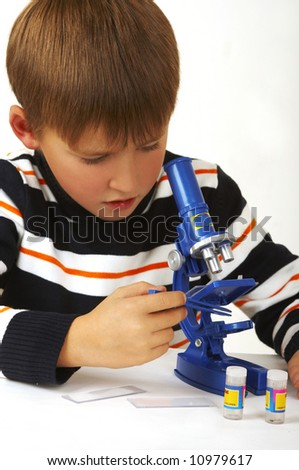 The boy with a microscope on a white background