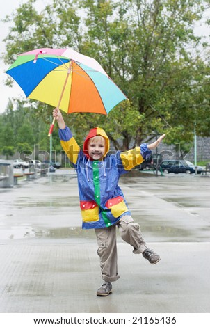The boy with an umbrella standing under a rain - stock photo