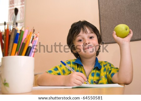 The boy with notebook and green apple and pen�il in the classroom - stock photo
