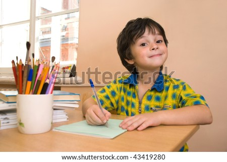 The boy with notebook and pencil in the classroom