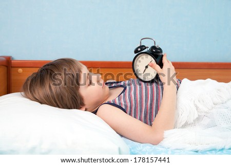 The boy with wake-up alarm in bed - stock photo