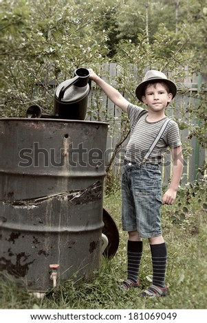 The boy with watering pot in garden - stock photo
