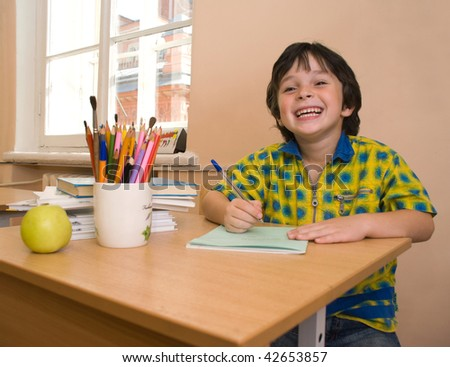 The boy with write-book and green apple and pencil in the classroom - stock photo
