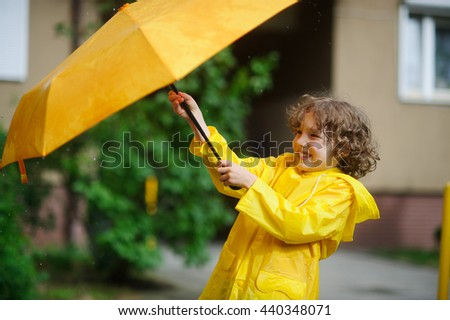 The boy 8-9 years in a bright yellow raincoat tries to hold an umbrella from wind flaws. He holds an umbrella with two hands. Child is in the yard of the house. He has a good mood - stock photo