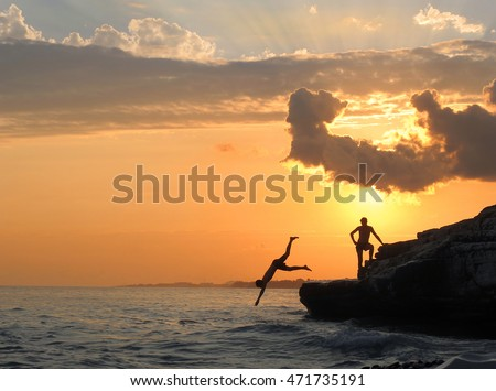 The boys jump from the coastal cliffs on the coast of the Black Sea