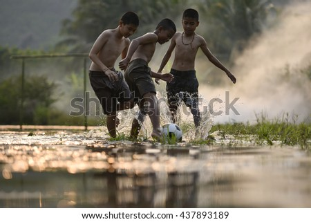 The boys play soccer on a shallow river .