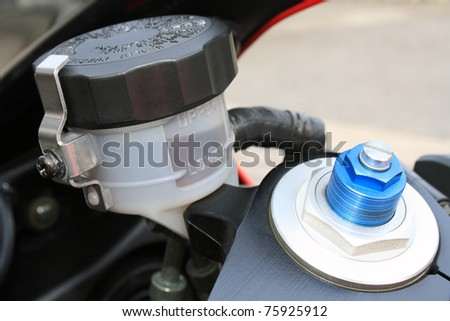 The brake oil level and the adjustable front suspension screw of a modern motorbike - stock photo