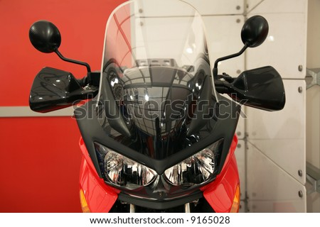 The brand new black-red motorcycle costs in an interior - stock photo
