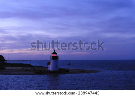 The Brant Point Lighthouse at the entrance to Nantucket Harbor at sunset. Beautiful travel scene at night. Brant Point Light House is the shortest lighthouse in New England. - stock photo