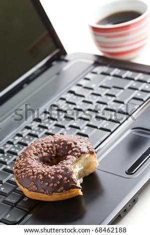 the break in the  office . doughnut on laptop keyboard - stock photo